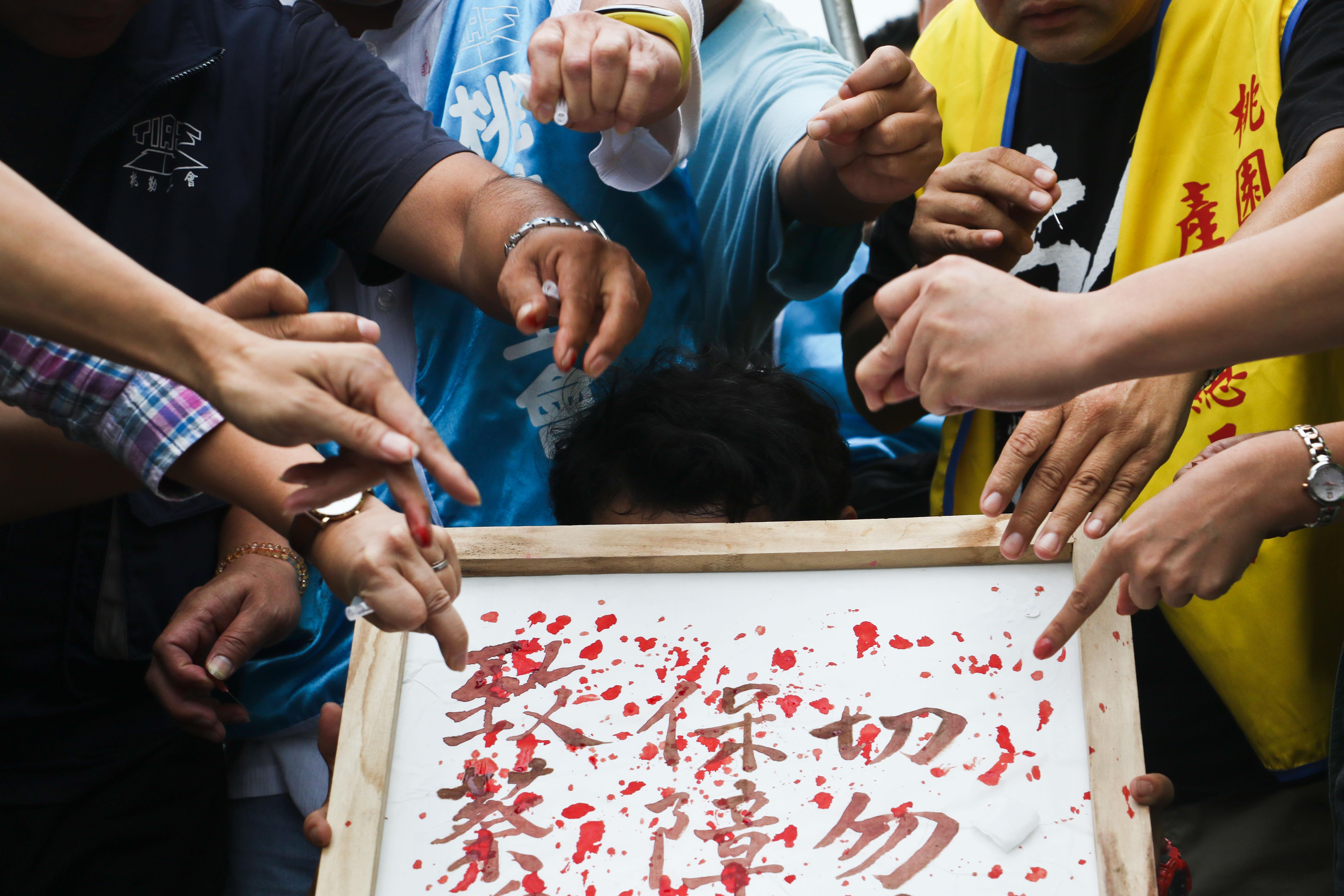 工會成員將血滴在血書之上